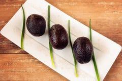 Foto del primo piano di interi avocado freschi e della cipolla fresca nel piatto di porcellana bianco su fondo di legno marrone immagine stock libera da diritti