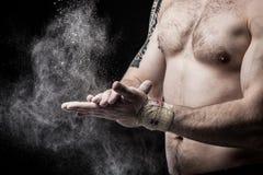 Foto del primo piano di un torso muscolare e delle mani isolati sulla b nera Fotografia Stock
