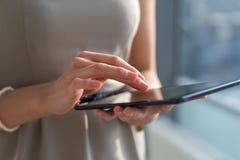 Foto del primo piano di una donna di affari con la compressa digitale in mani Mani femminili che scrivono, mandanti un sms e mess fotografia stock