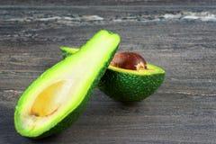 Foto del primo piano del taglio alla metà, semi marroni dell'avocado visibili su fondo di legno grigio fotografia stock libera da diritti