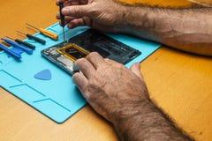 Foto del primo piano del tecnico Hand Repairing Cellphone fotografie stock libere da diritti