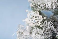 Foto del `s del Año Nuevo el árbol del ` s del Año Nuevo con la imitación de la nieve se adorna con el toyson un fondo azul Foto de archivo
