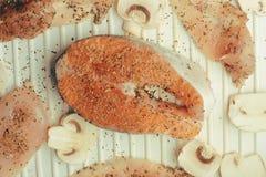 Foto del salmone Colore ricco del pesce rosso fresco Funghi e raccordo del pollo sulla griglia in spezie, basilico secco, sale, p immagine stock