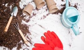 Foto del suelo superior para las plantas de trasplante, rastrillo, cucharada, regadera, guantes rojos Imágenes de archivo libres de regalías