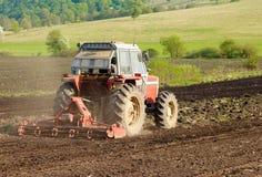 Foto del trattore rosso che lavora la terra Immagine Stock Libera da Diritti