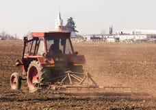 Foto del trattore rosso che lavora la terra Immagine Stock