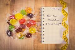 Foto del vintage, Años Nuevos de resoluciones escritas en cuaderno, caramelos y cinta métrica Foto de archivo libre de regalías