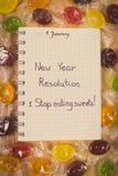 Foto del vintage, Años Nuevos de resoluciones escritas en cuaderno y caramelos coloridos Imagen de archivo libre de regalías
