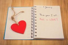 Foto del vintage, Años Nuevos de resoluciones escritas en cuaderno y corazón de madera rojo Imagen de archivo libre de regalías