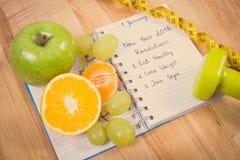 Foto del vintage, Años Nuevos de resoluciones escritas en cuaderno y frutas, pesas de gimnasia con centímetro Imágenes de archivo libres de regalías