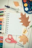 Foto del vintage, accesorios de la escuela y hojas de la naranja en los tableros blancos, de nuevo a concepto de la escuela Fotografía de archivo