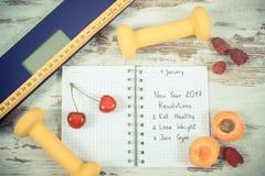 Foto del vintage, báscula de baño electrónica y resoluciones del Año Nuevo escritas en cuaderno Imagenes de archivo