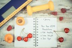 Foto del vintage, báscula de baño electrónica y resoluciones del Año Nuevo escritas en cuaderno Fotografía de archivo