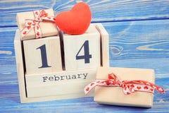 Foto del vintage, calendario del cubo con fecha el 14 de febrero, regalos y corazón rojo, día de tarjetas del día de San Valentín Fotos de archivo
