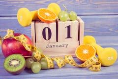 Foto del vintage, calendario del cubo con la fecha del 1 de enero, frutas, pesas de gimnasia y cinta métrica, Años Nuevos de reso Fotografía de archivo libre de regalías