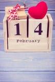 Foto del vintage, calendario del cubo con el regalo y corazón rojo, día de tarjetas del día de San Valentín Imagen de archivo