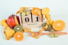 Foto del vintage, calendario del cubo, frutas, pesas de gimnasia y cinta métrica, Años Nuevos de resoluciones Imagen de archivo