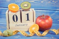 Foto del vintage, calendario del cubo, frutas y cinta métrica, Años Nuevos de resoluciones Imagen de archivo