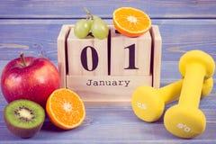 Foto del vintage, calendario del cubo, frutas y pesas de gimnasia, Años Nuevos de resoluciones, forma de vida sana Foto de archivo libre de regalías