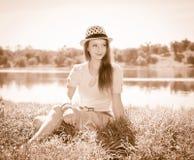 Foto del vintage de la mujer joven relajante en naturaleza Po diseñado retro Imagen de archivo libre de regalías