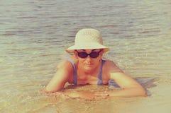 Foto del vintage de la mujer que miente en agua de mar baja Fotos de archivo libres de regalías