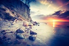 Foto del vintage de la orilla de mar rocosa hermosa en la salida del sol Foto de archivo