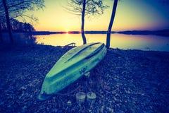 Foto del vintage de la puesta del sol hermosa sobre los barcos tranquilos del lago y del pescador Fotos de archivo