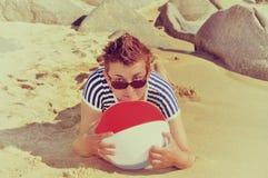 Foto del vintage de una mujer que miente en una playa arenosa Imágenes de archivo libres de regalías