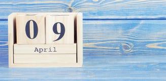 Foto del vintage, el 9 de abril Fecha del 9 de abril en calendario de madera del cubo Imagen de archivo libre de regalías