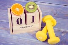 Foto del vintage, el 1 de enero en el calendario del cubo, las frutas y las pesas de gimnasia, Años Nuevos de resoluciones, forma Fotografía de archivo