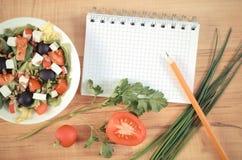 Foto del vintage, ensalada griega con las verduras y libreta para las notas, nutrición sana imagen de archivo libre de regalías