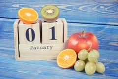 Foto del vintage, fecha del 1 de enero en calendario del cubo y frutas, Años Nuevos de resoluciones de la forma de vida sana Foto de archivo