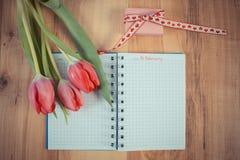 Foto del vintage, fecha del 14 de febrero en cuaderno, tulipanes frescos y regalo envuelto, día de tarjetas del día de San Valent Foto de archivo libre de regalías