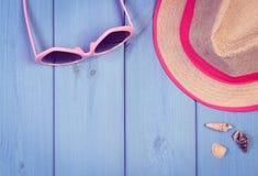 Foto del vintage, gafas de sol rosadas y sombrero de paja en los tableros de madera azules, accesorios para el verano Imagen de archivo