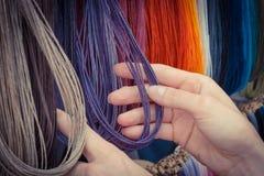 Foto del vintage, mano de la mujer con el collar colorido en parada en el bazar Fotografía de archivo