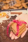 Foto del vintage, mano de la mujer con el pan de jengibre o galletas por tiempo de la Navidad y accesorios para cocer Fotos de archivo libres de regalías