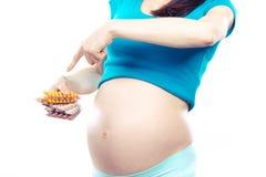 Foto del vintage, mujer en la pila embarazada de la demostración de píldoras médicas o suplementos, usando las vitaminas durante  Imagenes de archivo
