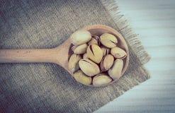 Foto del vintage, nueces de pistacho con la cuchara en la tabla de madera blanca, consumición sana Imágenes de archivo libres de regalías
