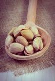 Foto del vintage, nueces de pistacho con la cuchara en la tabla de madera blanca, consumición sana Fotografía de archivo libre de regalías
