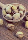 Foto del vintage, nueces de pistacho con la cuchara en la tabla de madera, consumición sana Fotos de archivo libres de regalías