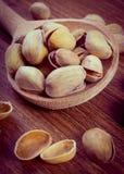 Foto del vintage, nueces de pistacho con la cuchara en la tabla de madera, consumición sana Fotos de archivo