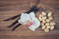 Foto del vintage, nueces de pistacho, orquídea floreciente y palillos fragantes de la vainilla, ingredientes cosméticos imágenes de archivo libres de regalías