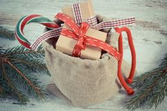 Foto del vintage, regalos con las cintas para la Navidad o tarjetas del día de San Valentín en bolso del yute y ramas spruce Fotos de archivo