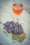 Foto del vintage, uvas con la hoja y vidrio de vino en la tabla de madera en jardín Imagen de archivo libre de regalías