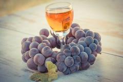 Foto del vintage, uvas con la hoja y vidrio de vino en la tabla de madera en jardín Foto de archivo