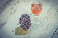 Foto del vintage, uvas con la hoja y vidrio de vino en la tabla de madera en jardín Fotos de archivo libres de regalías