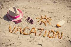 Foto del vintage, vacaciones de la palabra, accesorios para tomar el sol y pasaporte en la arena en la playa, tiempo de verano Fotos de archivo