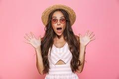 Foto del yelli precioso de las gafas de sol de la mujer que lleva 20s y del sombrero de paja fotografía de archivo