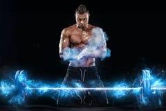 Foto dell'uomo atletico del forte culturista muscolare che pompa sui muscoli con il bilanciere su fondo nero Energia di allenamen immagini stock