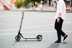 Foto dell'uomo moderno con il motorino elettrico alla via immagine stock libera da diritti